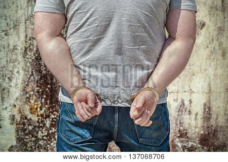 Man locked in handcuffs near wall .