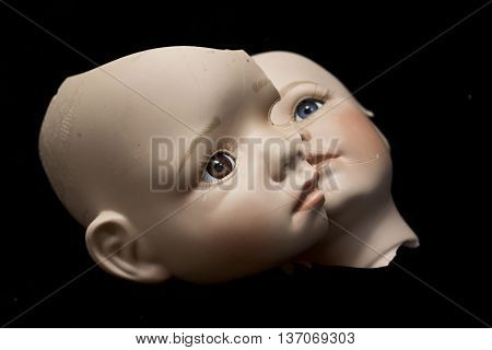 Broken Doll Body Parts on Black Background