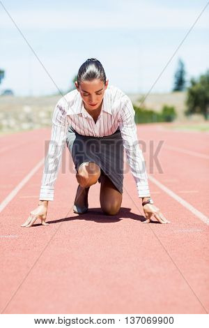 Businesswoman in ready to run position on running track
