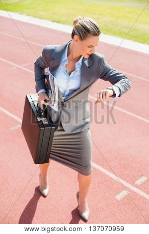 Businesswoman with briefcase in ready to run position on running track