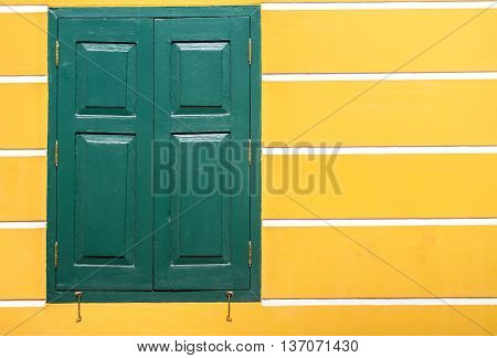 window green frame on an old yellow stucco wall with white line on background texture pattern vintage