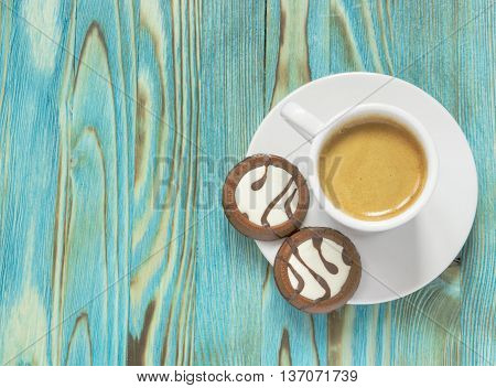 A photo of white cup with coffee and chocolate cakes on a blue wooden table. Morning still life photo tasty breakfast