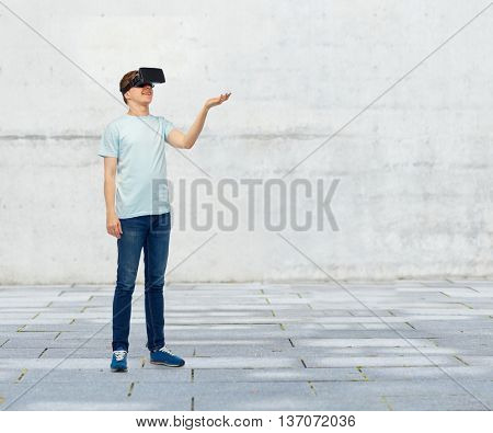 3d technology, virtual reality, entertainment, cyberspace and people concept - happy man with virtual reality headset or 3d glasses playing game and holding something on palm over street background