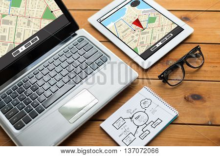 navigation, responsive design and technology concept - close up of on laptop computer, tablet pc, notebook and eyeglasses with gps navigator map and scheme on wooden table