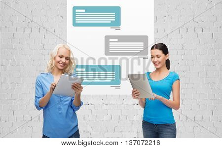 technology, internet communication and people concept concept - smiling women with tablet pc computer chatting and texting over messenger application background