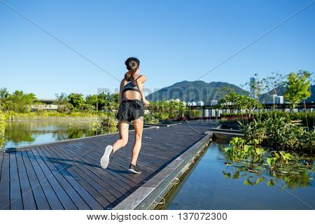 The back view of woman running in park