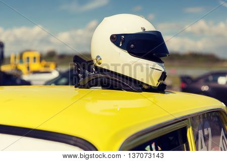 transportation, high speeds, racing and road concept - close up of car on autodrome or parking with helmet on roof top