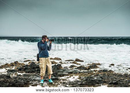 man taking photo on stony Lanzarote seashore in gloomy weather, Spain