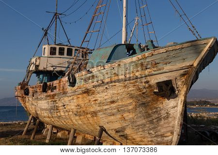 old abandoned schooner on the beach against blue sky