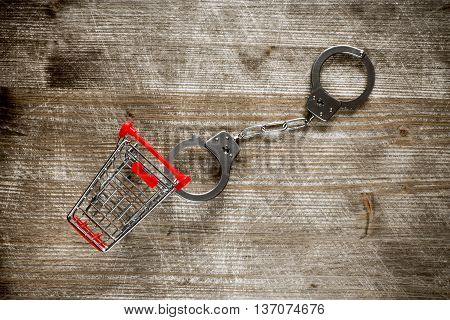 Shopping cart and handcuffs on old wooden background.Top view.