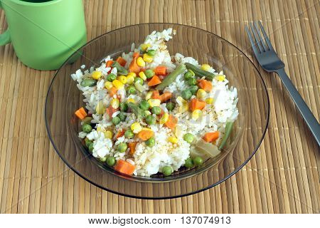 China white rise with vegetables in translucent plate on brown wicker straw mat metal spoon and green cup front view closeup