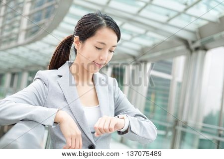 Asian business woman looking at smart watch