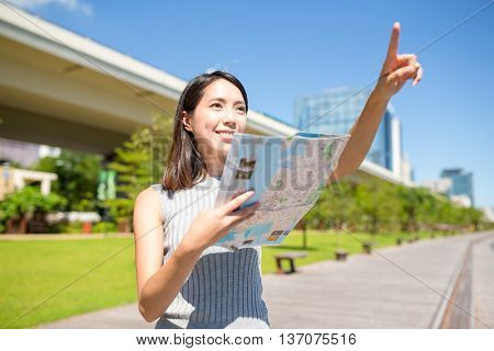 Woman holding a map and finger pointing far away