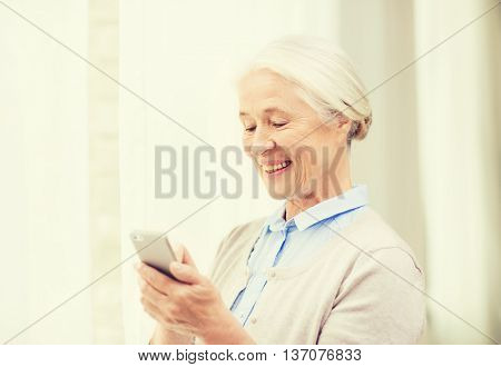 technology, communication age and people concept - happy senior woman with smartphone texting message at home