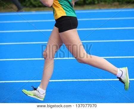 Legs Of Young Female Athlete Runs In Athletics Track