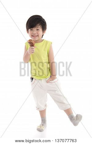 Cute asian boyeating roasted chicken leg on background