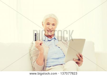 technology, online shopping, age and people concept - happy senior woman with tablet pc computer and credit or bank card at home