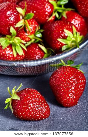 Washed strawberries in sieve with two fresh and juicy strawberries near it on stone background.