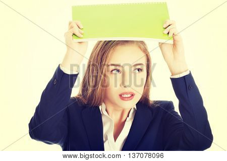Woman is holding notebook over her head