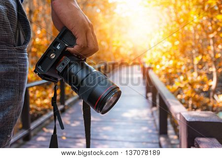 Photographer, camera on hand. work and travel concept.