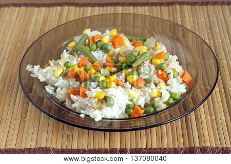 China white rise with vegetables in translucent plate on brown wicker straw mat and metal fork on left side front view closeup