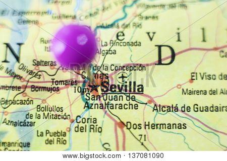 Pushpin marking on Seville Spain. Selective focus on city