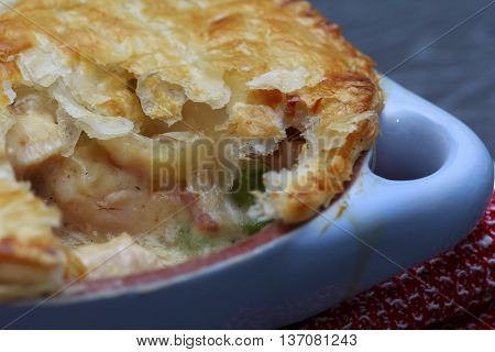 Chicken and bacon pot pie with cheese on wooden table