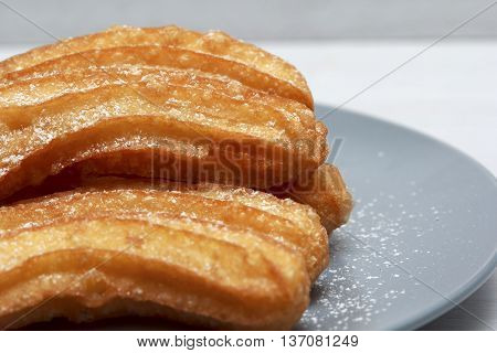 Churros on blue plate with chocolate sauce closeup