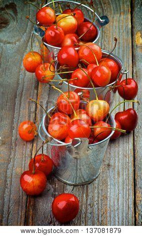 Two Tin Buckets Full of Ripe Sweet Maraschino Cherries closeup on Rustic Wooden background