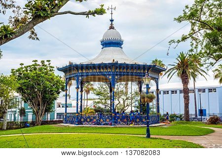 HAMILTON, BERMUDA MAY 25 - Children play wearing school uniforms by the old gazebo in Victoria Park on May 25 2016 in Hamilton Bermuda.
