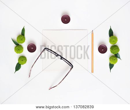 Paper, Pencil, Glasses And Candles With Decoration.