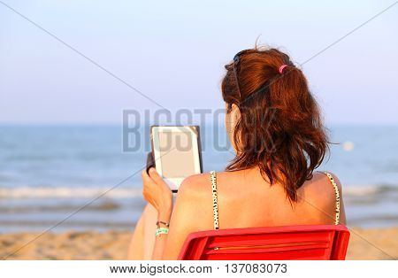 Pretty Woman On Red Chair Reads The Ebook On The Beach In Summer