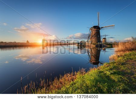 Beautiful traditional dutch windmills near the water channels with reflection in water at colorful sunrise in famous Kinderdijk Netherlands