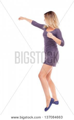 skinny woman funny fights waving his arms and legs. Rear view people collection.  backside view of person.  Isolated over white background. The girl in the purple dress fighting fists.