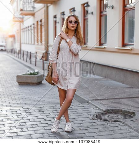 Beautiful Young Fashion Girl In Sunglasses, Handbags And Sneakers Standing On A Sunset Background