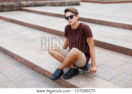 Young Guy In A T-shirt With Sunglasses And Shorts Sitting On A Skateboard.