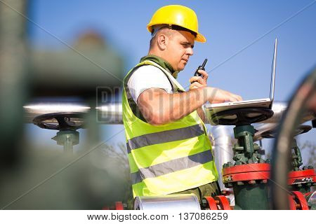 Engineer in worker's gear inspecting a valve