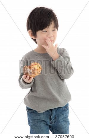 Cute asian boy eating cream puff on white background isolated