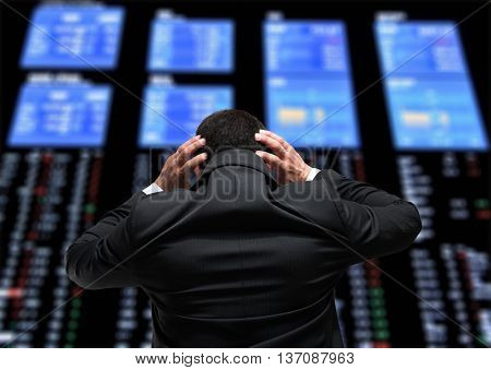 Desperate businessman looking at the stock exchange monitors