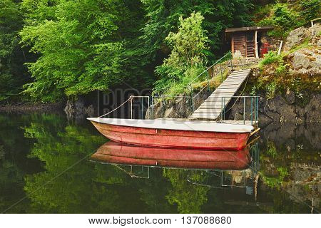Wooden pier and red boat on the river - reflection in the river