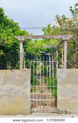 White iron garden gate at abandoned garden. Mallorca. Spain.