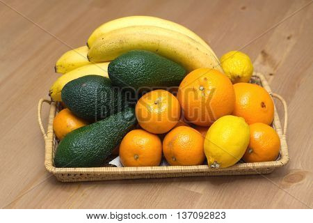 Still life with tropical fruits: bananas, avocados, lemons, oranges and tangerines lie on a brown wicker tray. Front photo closeup