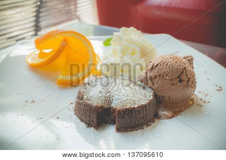 chocolate lava cake set with ice cream and sliced orange on white plate