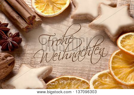 Lettering Frohe Weihnachten (german for Merry Christmas) on wood with Christmas spices, nuts and cookies