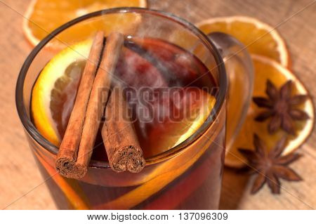 Mulled wine with spices on wooden table