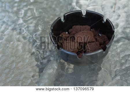 A black ashtray on the glass table