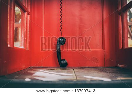black handset hanging in a red telephone box. telephone receiver hanging touching the floor in a red call telephone booth. the concept of technological progress and the development of communication. Hanging up