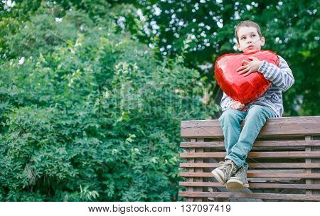 boy hugging a big red heart. child sitting in the park with a red balloon in the shape of a heart. the concept of first love. copy space for your text
