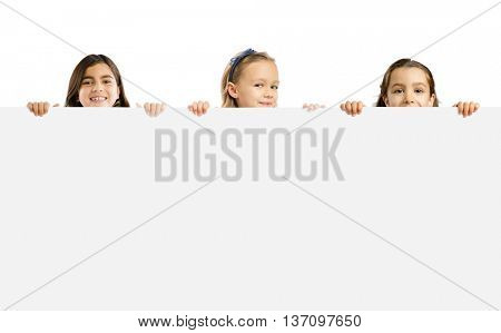 Cute litle girls holding a big white board with copyspace.