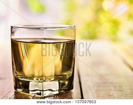Country drink. On wooden boards is glass with green transparent drink. A drink number one cold green tea. Country life. Light background.